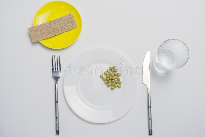 Adiete el concepto guisante en una placa blanca vacía con el cuchillo y la bifurcación foto de archivo