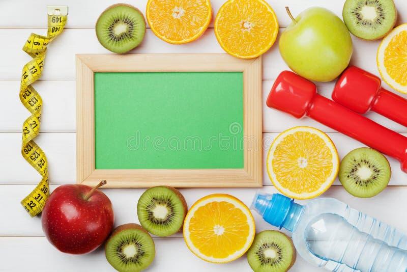 Adiete el plan, menú o programa, cinta métrica, agua, las pesas de gimnasia y comida de la dieta de frutas frescas en el fondo bl fotos de archivo