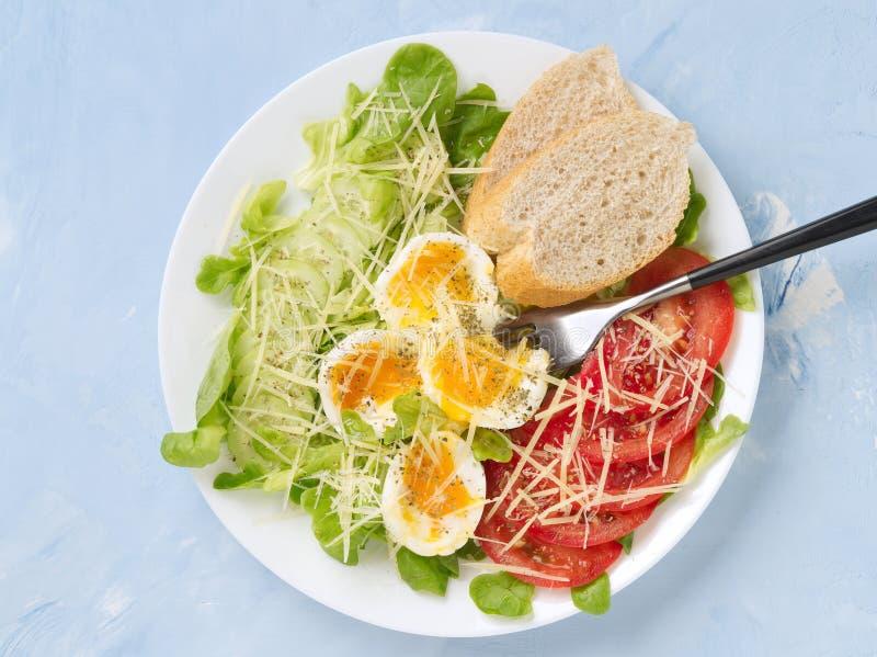 Adiete la ensalada con los huevos hervidos suavidad, el queso rallado y las verduras - tomates, lechuga Fondo ligero azul, visión foto de archivo libre de regalías