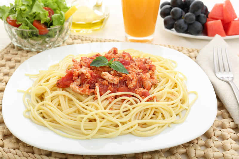 Adiete los espaguetis boloñés con la carne blanca y la fruta imagen de archivo libre de regalías
