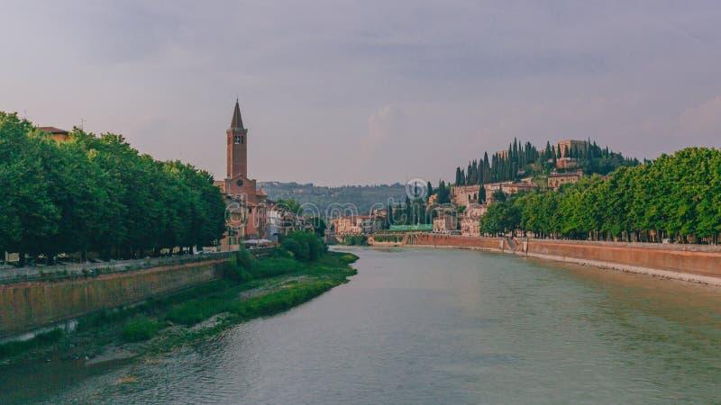 Adige flod vid den historiska mitten av Verona, Italien, med klockatornet av kyrkan av Santa Anastasia arkivbild