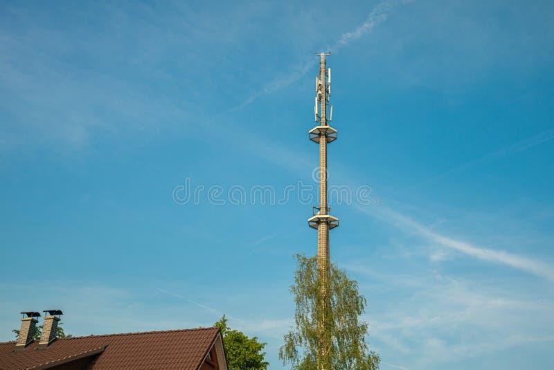 Adio mast för mobiltelefonnätverkstornen ovanför en bostads- byggnad in i den blåa himlen i ett bostadsområde royaltyfri bild
