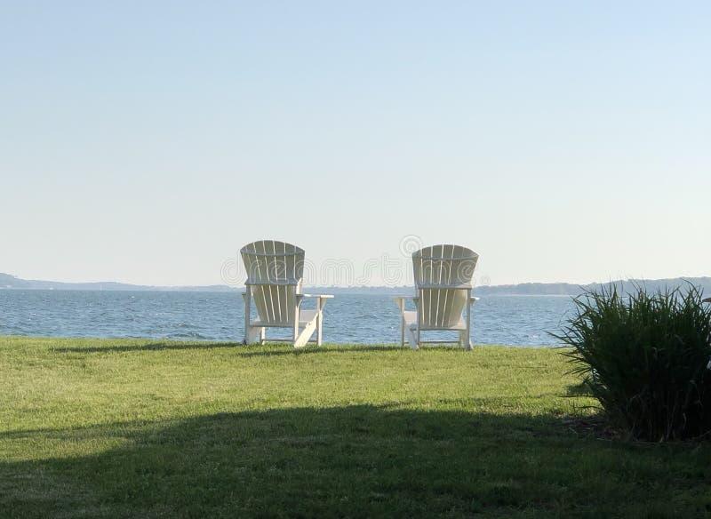 Adirondack blanco gemelo preside la playa en luz del sol fotografía de archivo libre de regalías