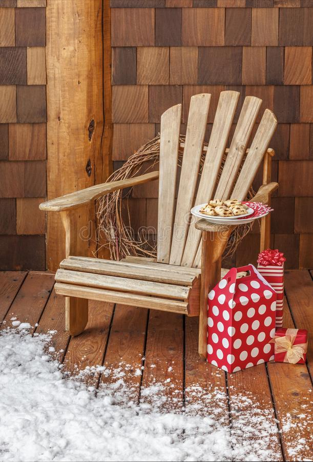 Adirondack chair with Christmas gifts on the snowy wooden porch deck of a rustic country cabin. Winter holiday vacation homes. Adirondack chair with Christmas royalty free stock image