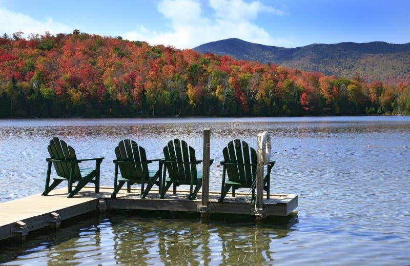 Adirondack chairs on lake royalty free stock photography