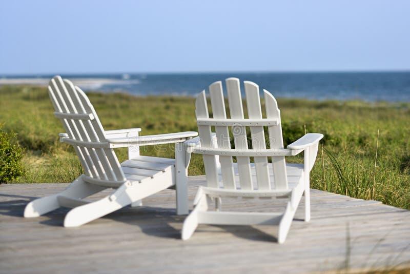 Adirondack chairs overlooking beach. stock photo