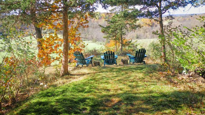 Adirondack Chairs on Scenic Overlook in Fall. Three teal Adirondack chairs sitting on a scenic overlook ledge in the driftless region of Wisconsin royalty free stock photos