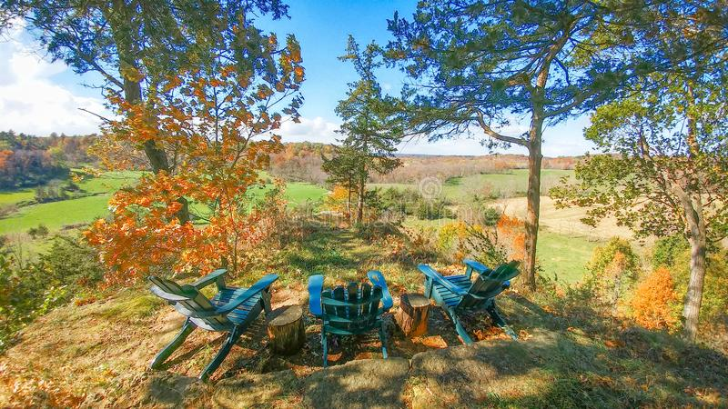 Adirondack Chairs on Scenic Overlook in Fall. Three teal Adirondack chairs sitting on a scenic overlook ledge in the driftless region of Wisconsin royalty free stock images