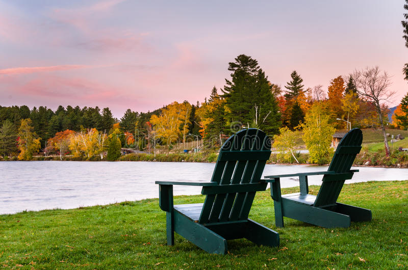 Adirondack Chairs on the Shore of Mirror Lake in the Village of Lake Placid, NY. Two Green Adirondack Chair near the Shore of a Lake at Dusk. Beautiful Autumnal stock image