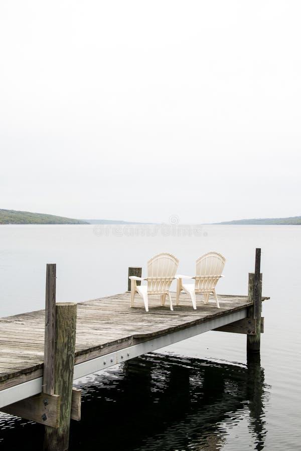 Adirondack preside en un muelle en Seneca Lake New York imagen de archivo libre de regalías