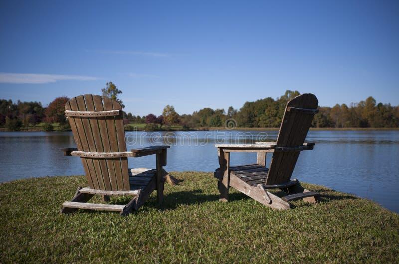 Adirondack sitzt nahe bei einem See im Herbst vor stockbilder