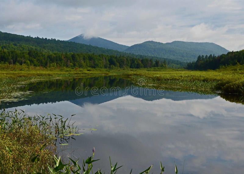 Adirondack wilderness waterway and mountains landscape. The Kunjamuck River waterway view of Dug and East Mountains stock photography