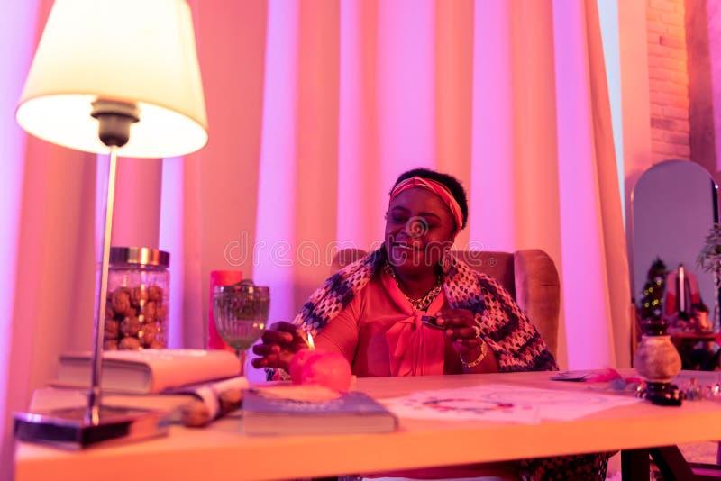 Adivinho afro-americano que ilumina a vela no salão de beleza espiritual imagens de stock