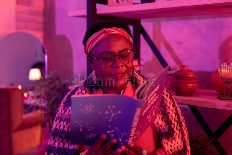 Adivinho gordo afro-americano com anéis grandes que lê um livro na adivinhação imagens de stock royalty free