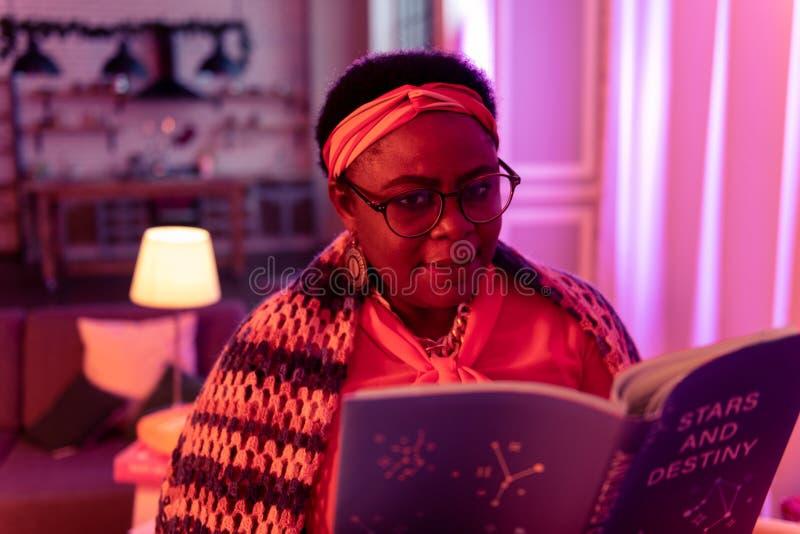 Adivinho gordo afro-americano com os anéis grandes que guardam um livro na astrologia imagem de stock