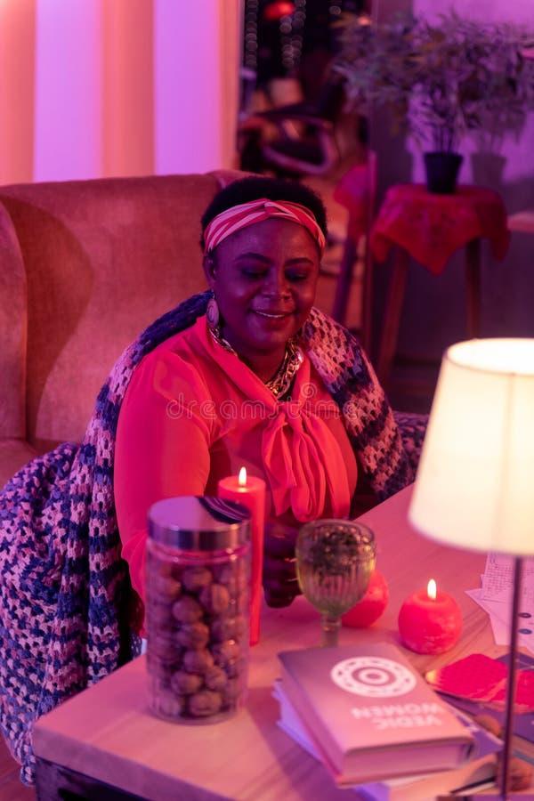 Adivinho gordo afro-americano em ornamentações étnicas que prepara-se para o trabalho fotografia de stock