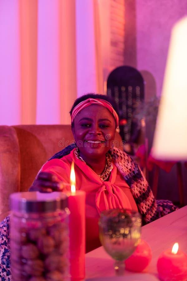 Adivinho gordo afro-americano em ornamentações étnicas que sorri agradavelmente fotografia de stock royalty free