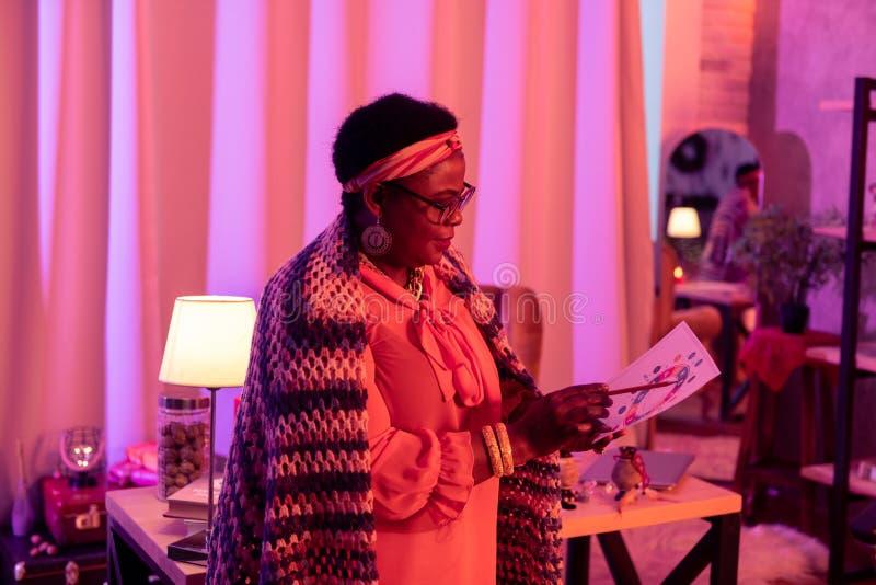 Adivinho gordo afro-americano em um funcionamento de lã brilhante do xaile na carta do nascimento fotos de stock