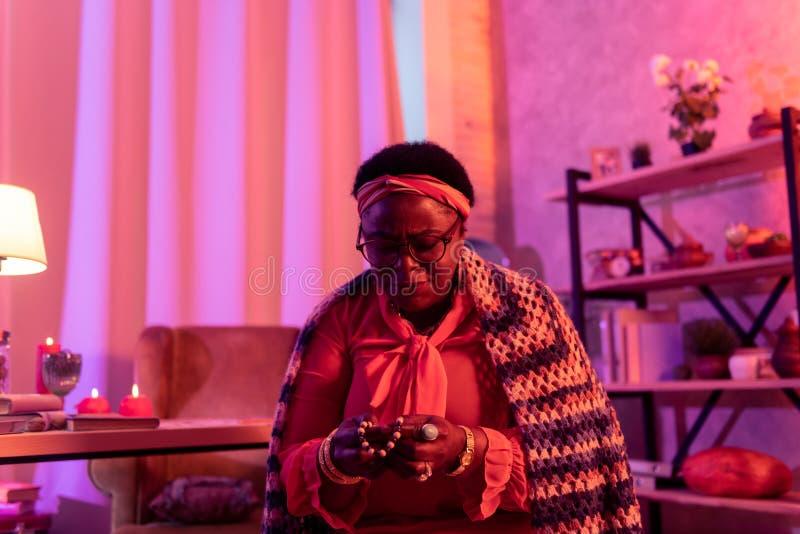 Adivinho gordo afro-americano em um xaile de lã brilhante que guarda uma corda de grânulos fotografia de stock