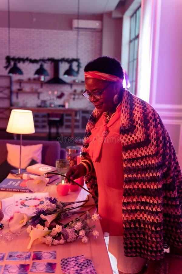 Adivinho gordo afro-americano no eyewear que guarda uma flor em sua mão imagens de stock royalty free