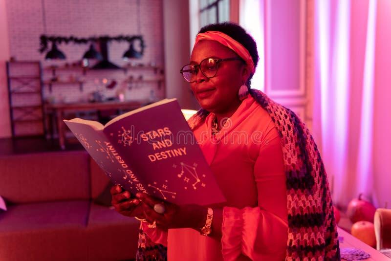 Adivinho gordo afro-americano no eyewear que lê um livro na astrologia fotografia de stock
