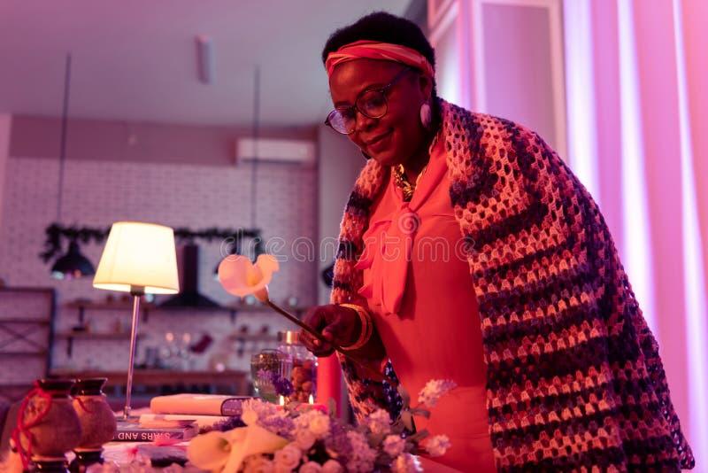 Adivinho gordo afro-americano no eyewear que toma uma flor fotos de stock royalty free