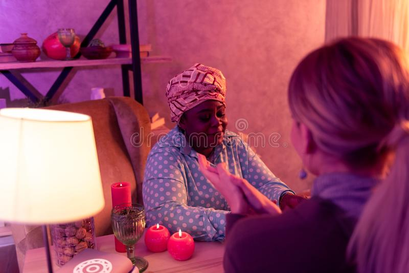 Adivinho gordo afro-americano no headwear étnico que fala ao cliente imagens de stock