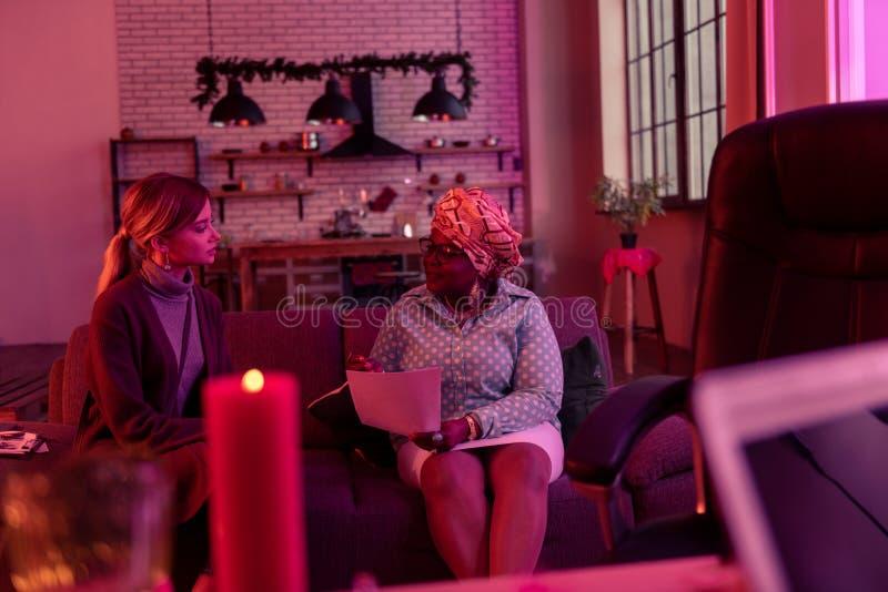 Adivinho gordo afro-americano no headwear étnico que senta-se no sofá com o cliente imagem de stock