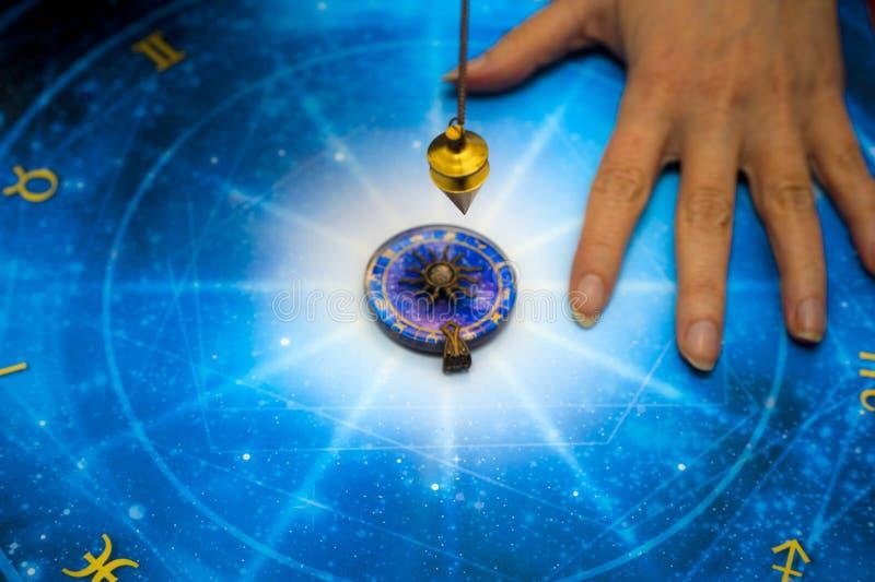 Adivino con el péndulo mágico en horóscopo azul como la astrología, zodiaco tema esotérico fotos de archivo