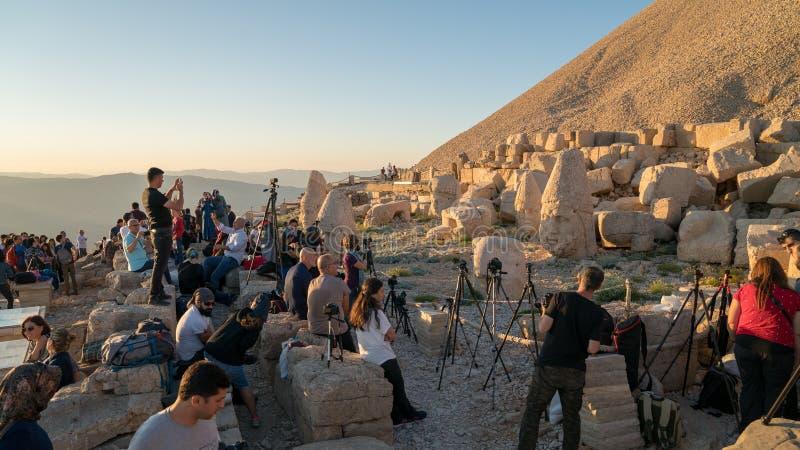 A group of photographers at the top of Nemrut Mountai near Commagene statue ruins waiting for sunset in Adiyaman, Turkey. Adiyaman, Turkey - July 2018: A group stock image