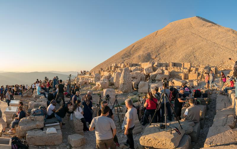 A group of photographers at the top of Nemrut Mountai near Commagene statue ruins waiting for sunset in Adiyaman, Turkey. Adiyaman, Turkey - July 2018: A group stock images