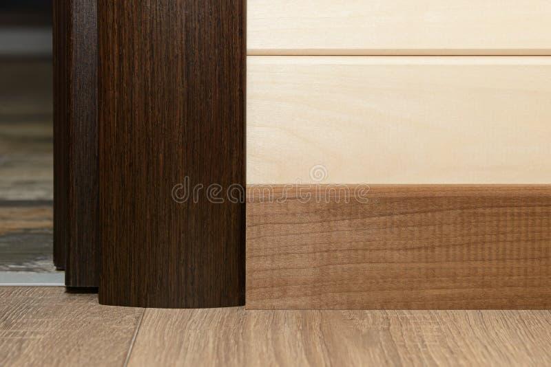 Adjacent laminate flooring, plinth and platbands of wood. Adjacent laminate flooring, plinth and platbands made of wood stock photos