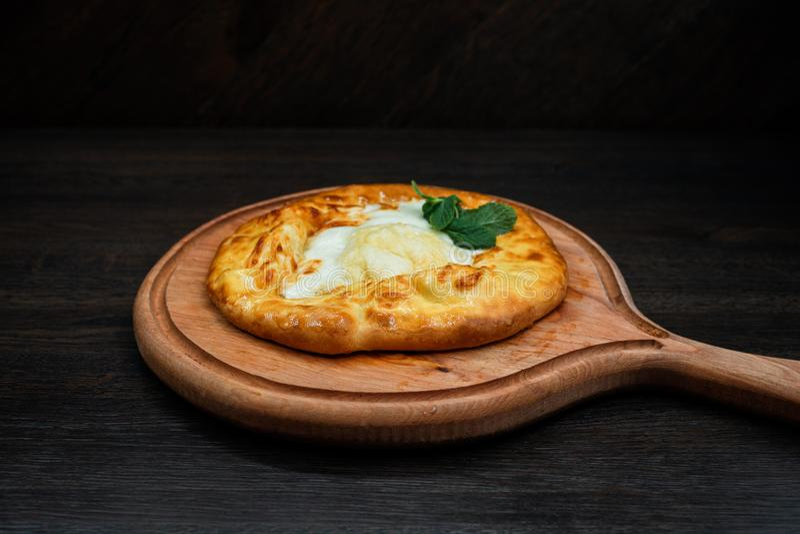 Adjara khachapuri with chicken egg on a wooden board in a restaurant. A popular Georgian national dish. Healthy food. stock photo