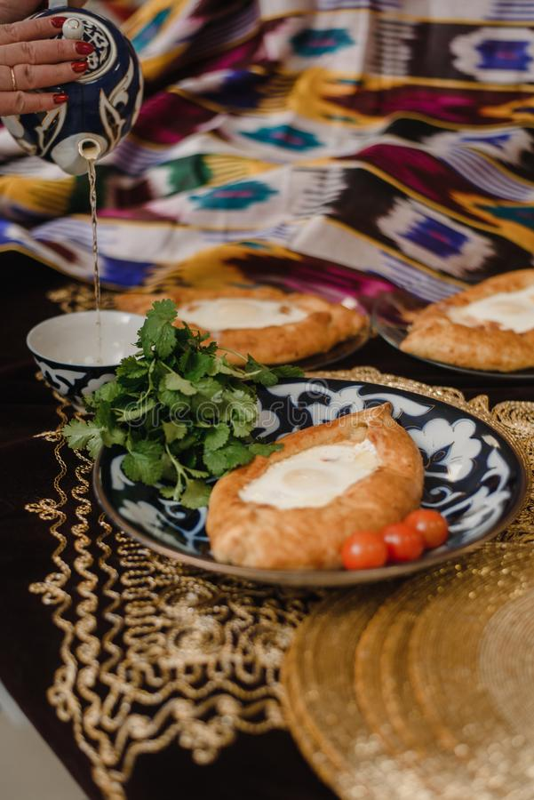Adjara khachapuri on the eastern table. egg in hot bread on oriental plates is in a restaurant royalty free stock photos