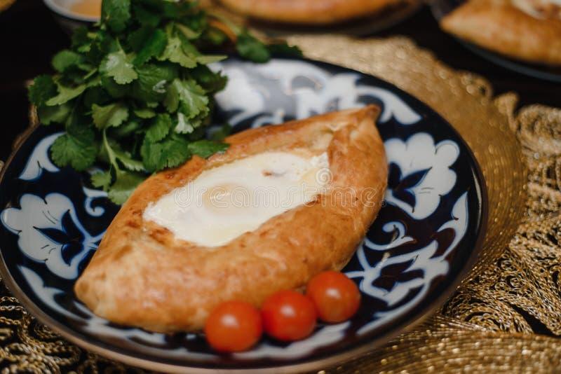 Adjara khachapuri on the eastern table. egg in hot bread on oriental plates is in a restaurant stock photos
