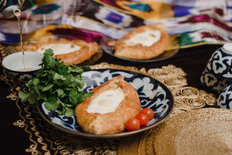 Adjara khachapuri på den östliga tabellen ägget i varmt bröd på orientaliska plattor är i en restaurang fotografering för bildbyråer