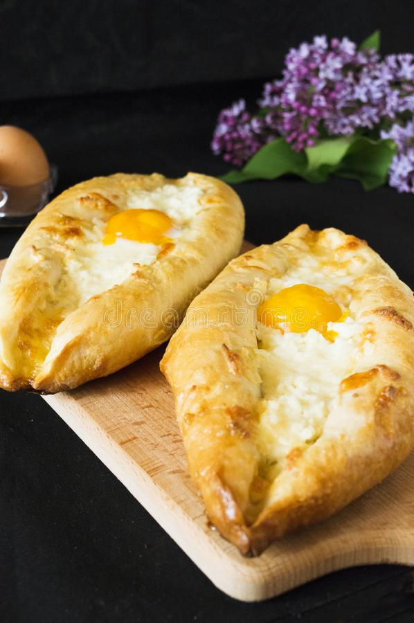 Adjara khachapuri with two types of cheese. Ajarian khachapuri with two types of cheese. Delicious pastries. Food photo. Lilac royalty free stock images