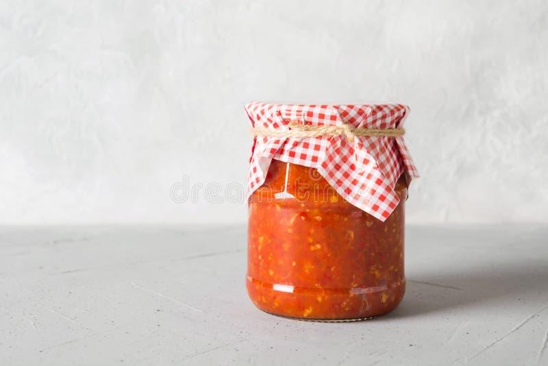 Adjika с томатами, чеснок соуса овоща, болгарские перцы в опарнике на светлой предпосылке стоковое фото