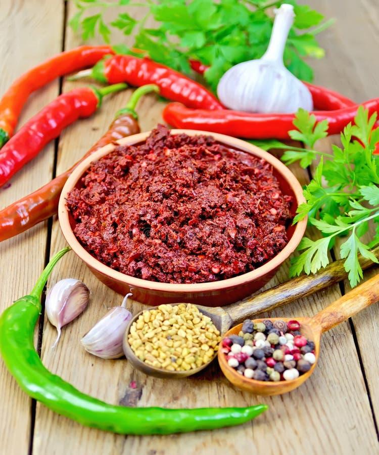 Adjika med varm peppar och kryddor ombord royaltyfri foto