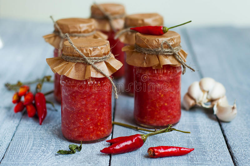 Adjika, red tomato sauce. Bitter red tomato sauce in a glass jar with paper and the twine around the bottle banks on the wooden table stock photography