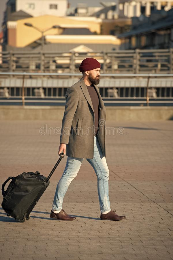 Adjust living in new city. Man bearded hipster travel with luggage bag on wheels. Traveler with suitcase arrive airport. Railway station urban background stock photo