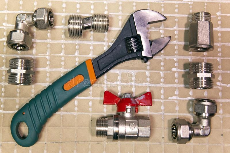 Adjust wrench power grip and elements of water and gas shutoff valves, flat lay.  stock photos
