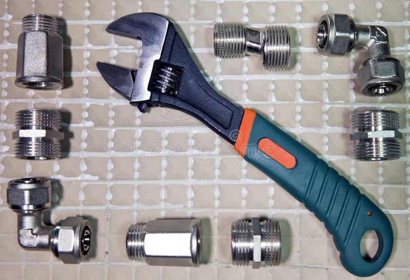 Adjust wrench power grip and elements of water and gas shutoff valves, flat lay.  royalty free stock images