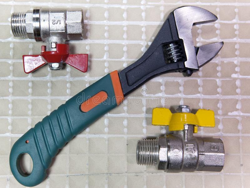 Adjust wrench power grip and elements of water and gas shutoff valves, flat lay.  royalty free stock photography