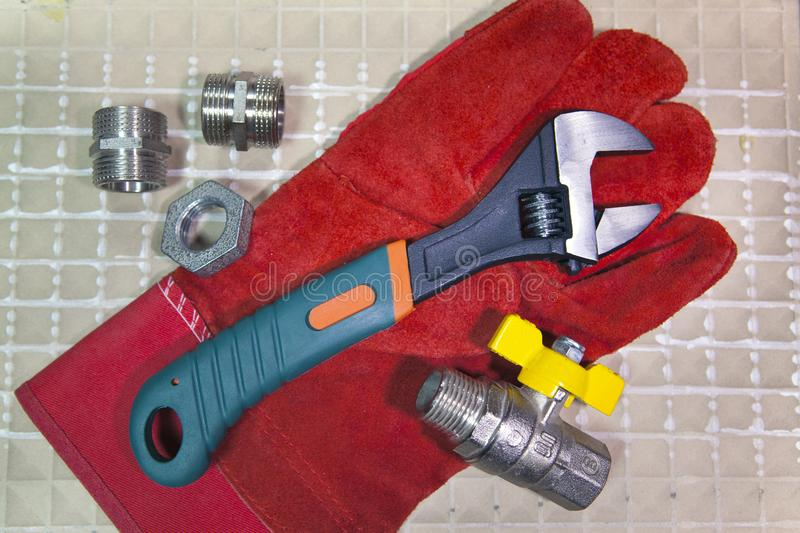 Adjust wrench power grip and elements of water and gas shutoff valves on a working protective glove, flat lay.  royalty free stock photography