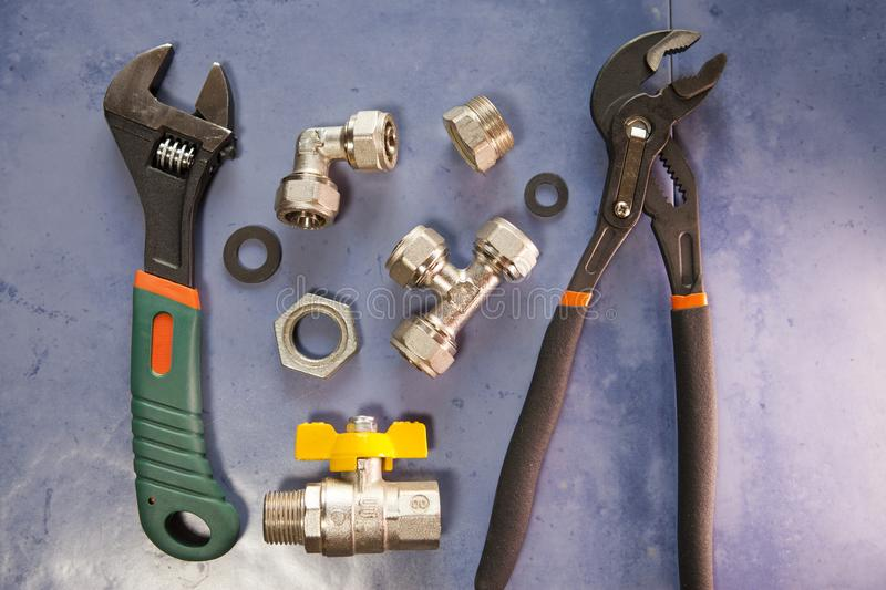 Adjust wrench power grip, groove joint pillers and elements of water and gas shutoff valves, flat lay.  stock photography