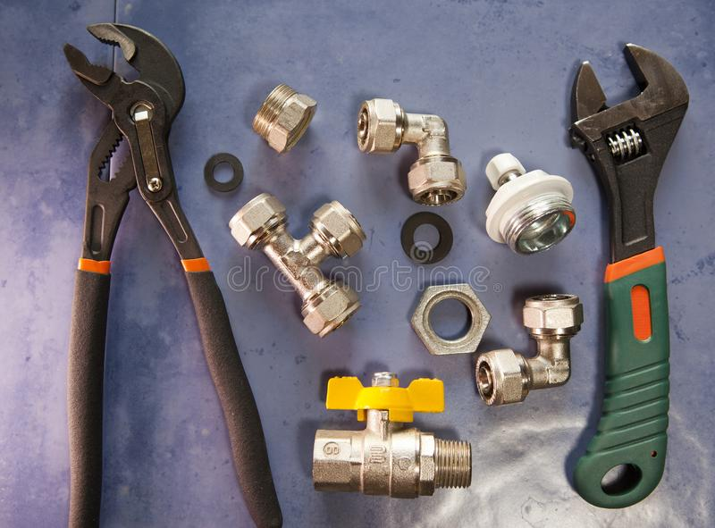 Adjust wrench power grip, groove joint pillers and elements of water and gas shutoff valves, flat lay.  stock photo