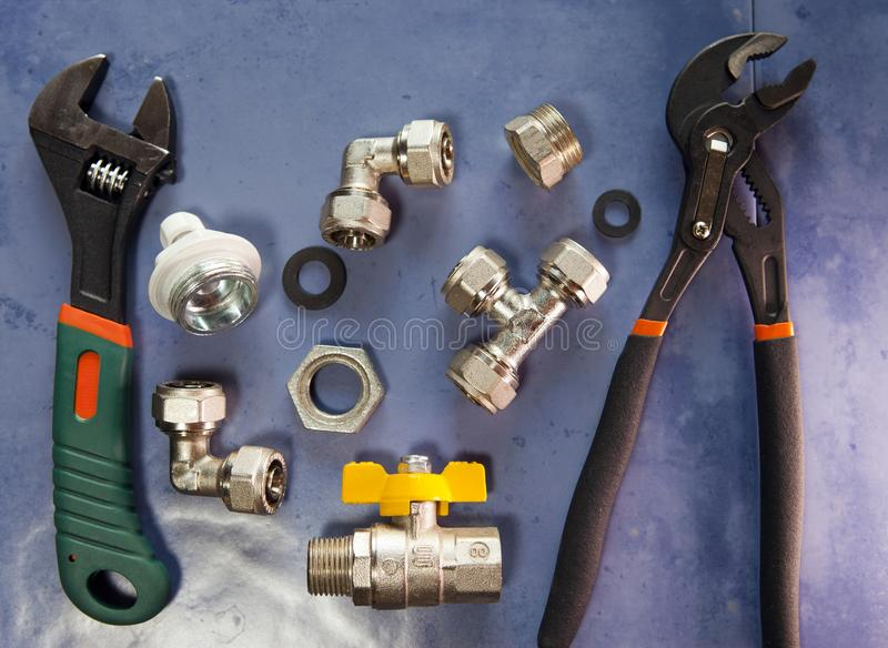 Adjust wrench power grip, groove joint pillers and elements of water and gas shutoff valves, flat lay.  stock images