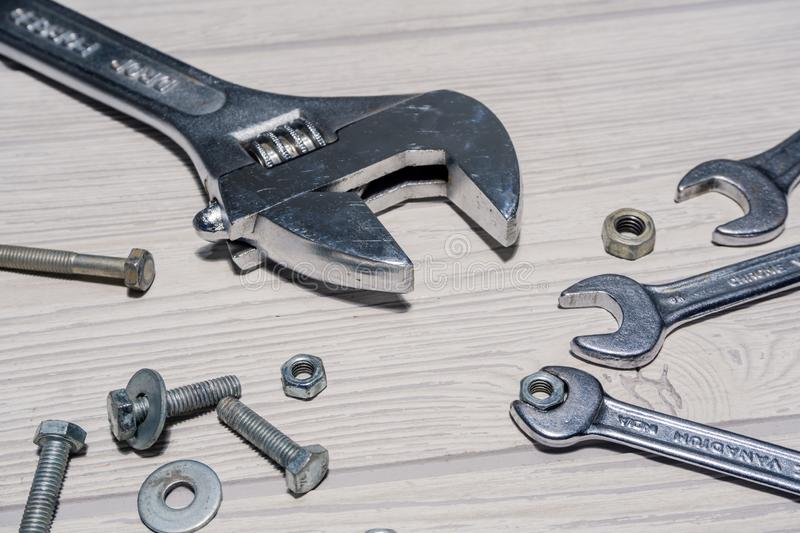 Adjustable and ordinary spanners, nuts and bolts on the table. Adjustable spanners and ordinary wrenches, nuts and bolts are on the table close up stock photos
