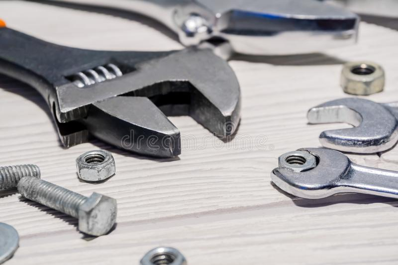 Adjustable and ordinary wrenches, nuts and bolts on the table. Adjustable spanners and ordinary wrenches, nuts and bolts are on the table close up stock image